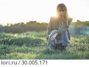 Купить «Fashionable young girl crouching in sheer dress and jacket», фото № 30005171, снято 26 апреля 2013 г. (c) Wavebreak Media / Фотобанк Лори