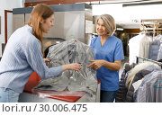 Купить «Fine worker giving woman her clean clothes», фото № 30006475, снято 22 января 2019 г. (c) Яков Филимонов / Фотобанк Лори