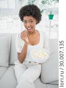 Купить «Attractive brunette eating popcorn sitting on cosy sofa», фото № 30007135, снято 7 июня 2013 г. (c) Wavebreak Media / Фотобанк Лори