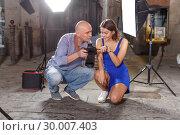Купить «Photographer showing photos on camera to model girl», фото № 30007403, снято 5 октября 2018 г. (c) Яков Филимонов / Фотобанк Лори