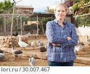 Купить «Smiling female farmer on poultry yard», фото № 30007467, снято 15 декабря 2018 г. (c) Яков Филимонов / Фотобанк Лори