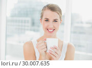 Купить «Smiling blond woman holding cup of coffee», фото № 30007635, снято 12 июня 2013 г. (c) Wavebreak Media / Фотобанк Лори