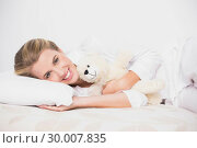 Купить «Cheerful cute model lying on cosy bed with teddy bear», фото № 30007835, снято 12 июня 2013 г. (c) Wavebreak Media / Фотобанк Лори