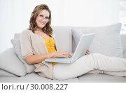 Купить «Smiling gorgeous model using laptop on cosy sofa», фото № 30008227, снято 5 июня 2013 г. (c) Wavebreak Media / Фотобанк Лори