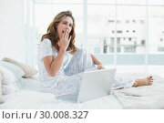 Tired woman sitting on cosy bed with laptop. Стоковое фото, агентство Wavebreak Media / Фотобанк Лори