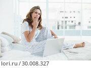 Купить «Tired woman sitting on cosy bed with laptop», фото № 30008327, снято 5 июня 2013 г. (c) Wavebreak Media / Фотобанк Лори