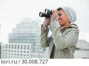 Купить «Smiling young model in winter clothes watching with binoculars», фото № 30008727, снято 29 мая 2013 г. (c) Wavebreak Media / Фотобанк Лори
