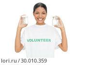 Купить «Smiling model wearing volunteer tshirt holding pots», фото № 30010359, снято 24 мая 2013 г. (c) Wavebreak Media / Фотобанк Лори