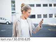Купить «Furious stylish businesswoman shouting at her phone», фото № 30010635, снято 11 июня 2013 г. (c) Wavebreak Media / Фотобанк Лори