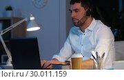 Купить «businessman in headset with laptop at night office», видеоролик № 30011159, снято 11 февраля 2019 г. (c) Syda Productions / Фотобанк Лори