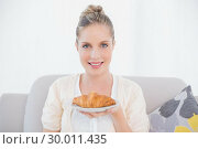Купить «Happy fresh model holding croissant sitting on sofa», фото № 30011435, снято 31 мая 2013 г. (c) Wavebreak Media / Фотобанк Лори