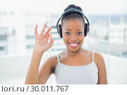 Купить «Smiling woman listening to music with headphones and shwoing okay sign », фото № 30011767, снято 28 мая 2013 г. (c) Wavebreak Media / Фотобанк Лори