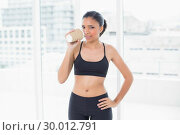 Купить «Pensive dark haired model in sportswear drinking coffee», фото № 30012791, снято 14 июня 2013 г. (c) Wavebreak Media / Фотобанк Лори