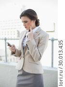 Купить «Troubled stylish brown haired businesswoman looking at her mobile phone», фото № 30013435, снято 18 июня 2013 г. (c) Wavebreak Media / Фотобанк Лори