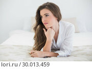 Купить «Thinking casual brown haired woman in white pajamas lying on her bed», фото № 30013459, снято 18 июня 2013 г. (c) Wavebreak Media / Фотобанк Лори