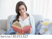 Peaceful casual brown haired woman in white pajamas reading a book. Стоковое фото, агентство Wavebreak Media / Фотобанк Лори