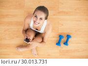 Купить «Smiling sporty brunette holding a mobile phone and sitting next to dumbbells», фото № 30013731, снято 19 июня 2013 г. (c) Wavebreak Media / Фотобанк Лори