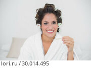 Купить «Smiling natural brunette holding thermometer», фото № 30014495, снято 21 июня 2013 г. (c) Wavebreak Media / Фотобанк Лори