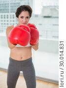 Купить «Determined brunette boxing and looking at camera», фото № 30014831, снято 21 июня 2013 г. (c) Wavebreak Media / Фотобанк Лори