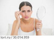 Купить «Serious young brown haired model in white pajamas plucking her eyebrows», фото № 30014959, снято 25 июня 2013 г. (c) Wavebreak Media / Фотобанк Лори