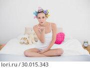 Купить «Seductive natural brown haired woman in hair curlers blowing a kiss to the camera», фото № 30015343, снято 26 июня 2013 г. (c) Wavebreak Media / Фотобанк Лори
