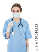Купить «Female doctor holding an injection and looking at it», фото № 30016883, снято 27 июня 2013 г. (c) Wavebreak Media / Фотобанк Лори