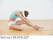 Beautiful slender woman wearing sportswear stretching her leg. Стоковое фото, агентство Wavebreak Media / Фотобанк Лори