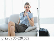 Купить «Chic businesswoman posing sitting on couch nest to her suitcase», фото № 30020035, снято 17 июля 2013 г. (c) Wavebreak Media / Фотобанк Лори