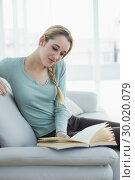 Купить «Content calm woman reading a book while sitting on couch», фото № 30020079, снято 17 июля 2013 г. (c) Wavebreak Media / Фотобанк Лори