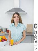 Купить «Content young woman posing in kitchen holding a glass of orange juice», фото № 30021679, снято 3 июля 2013 г. (c) Wavebreak Media / Фотобанк Лори