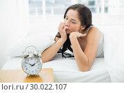 Купить «Thoughtful woman in bed with alarm clock in foreground», фото № 30022107, снято 10 июля 2013 г. (c) Wavebreak Media / Фотобанк Лори