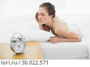 Купить «Sleepy woman in bed with alarm clock in foreground», фото № 30022571, снято 12 июля 2013 г. (c) Wavebreak Media / Фотобанк Лори