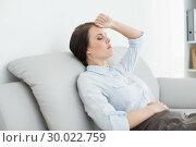 Купить «Serious well dressed woman sitting on sofa», фото № 30022759, снято 12 июля 2013 г. (c) Wavebreak Media / Фотобанк Лори