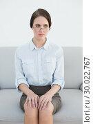 Купить «Displeased well dressed woman sitting on sofa», фото № 30022767, снято 12 июля 2013 г. (c) Wavebreak Media / Фотобанк Лори