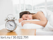 Купить «Woman sleeping in bed with alarm clock in foreground», фото № 30022791, снято 16 июля 2013 г. (c) Wavebreak Media / Фотобанк Лори