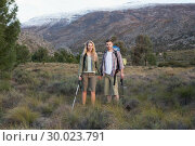 Купить «Couple with backpacks and trekking poles against mountain», фото № 30023791, снято 20 августа 2013 г. (c) Wavebreak Media / Фотобанк Лори
