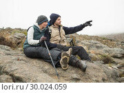Купить «Couple sitting on rock with trekking poles while on a hike», фото № 30024059, снято 21 августа 2013 г. (c) Wavebreak Media / Фотобанк Лори