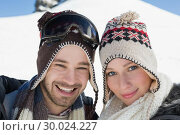 Купить «Smiling couple in woolen hats on snow covered landscape», фото № 30024227, снято 22 августа 2013 г. (c) Wavebreak Media / Фотобанк Лори