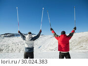Купить «Rear view of a couple raising ski poles on snow», фото № 30024383, снято 22 августа 2013 г. (c) Wavebreak Media / Фотобанк Лори