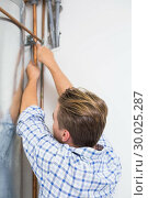Купить «Technician servicing an hot water heater pipes», фото № 30025287, снято 25 июля 2013 г. (c) Wavebreak Media / Фотобанк Лори