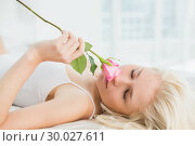 Купить «Close up of pretty young woman in bed with a rose», фото № 30027611, снято 6 августа 2013 г. (c) Wavebreak Media / Фотобанк Лори