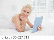 Купить «Smiling casual young blond with tablet PC in bed», фото № 30027711, снято 6 августа 2013 г. (c) Wavebreak Media / Фотобанк Лори