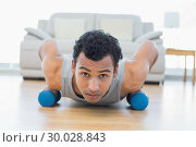 Man with dumbbells doing push ups in the living room. Стоковое фото, агентство Wavebreak Media / Фотобанк Лори