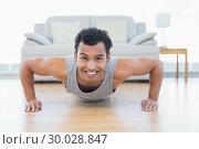 Sporty smiling man doing push ups in the living room. Стоковое фото, агентство Wavebreak Media / Фотобанк Лори