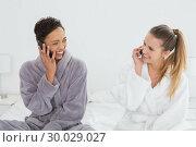 Купить «female friends in bathrobes using phones on bed», фото № 30029027, снято 13 августа 2013 г. (c) Wavebreak Media / Фотобанк Лори