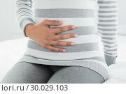 Купить «Mid section of a woman with stomach pain sitting in bed», фото № 30029103, снято 13 августа 2013 г. (c) Wavebreak Media / Фотобанк Лори