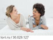 Купить «Two relaxed smiling female friends lying in bed», фото № 30029127, снято 13 августа 2013 г. (c) Wavebreak Media / Фотобанк Лори