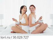 Купить «Two smiling female friends with bowls sitting on bed», фото № 30029727, снято 15 августа 2013 г. (c) Wavebreak Media / Фотобанк Лори