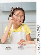 Купить «Portrait of a smiling young girl holding cookie mold in kitchen», фото № 30029943, снято 29 августа 2013 г. (c) Wavebreak Media / Фотобанк Лори