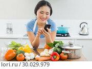 Купить «Smiling woman text messaging in front of vegetables in kitchen», фото № 30029979, снято 29 августа 2013 г. (c) Wavebreak Media / Фотобанк Лори
